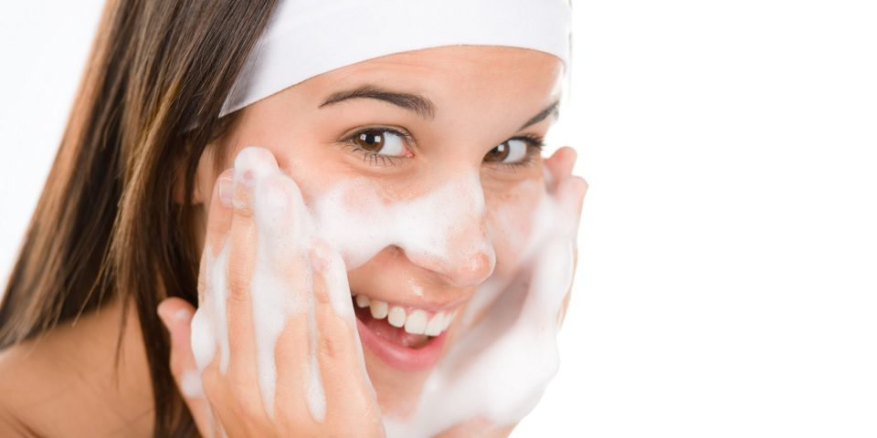 woman washes face with cleansing foam