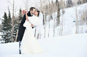 bride and groom kissing on the snow