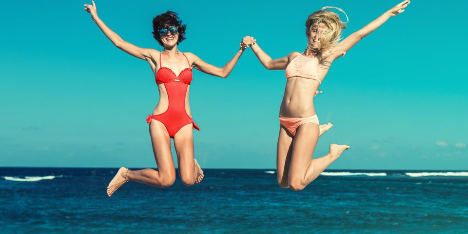 women in bikinis jumping on the beach